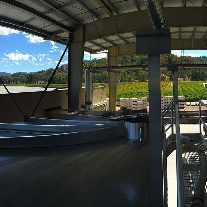 Tanks with a vineyard view at winemaking location in Hopland