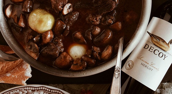 Beef Bourguignon stew in a bowl with french bread and Decoy Merlot