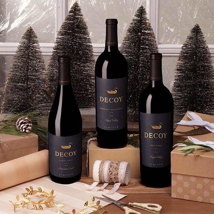 Three bottles of Decoy Limited wine bottles on a gift wrapping table