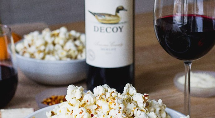 Spicy popcorn with a glass of decoy merlot on table