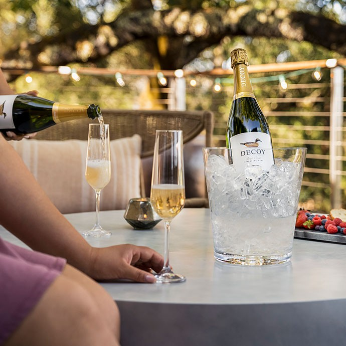Decoy Sparkling with two glasses of wine next to a firepit