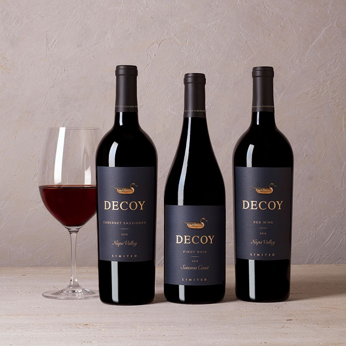 Three decoy limited wines with a glass of wine